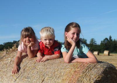 Kinder auf den frischgepressten Strohballen